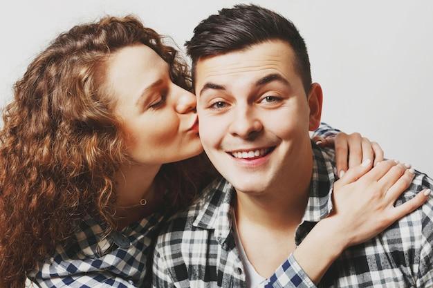 Bliska portret czule młodej modelki całuje swojego chłopaka i obejmuje się namiętnie, demonstruje swoją miłość i oddanie