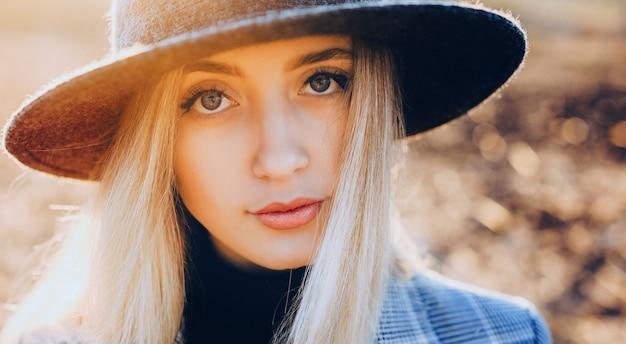 Bliska portret damy z blond włosami, patrząc na kamery w kapeluszu