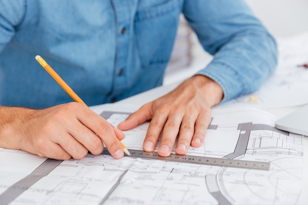 Bliska portret dłoni trzymających linijkę i ołówek nad sheme na stole