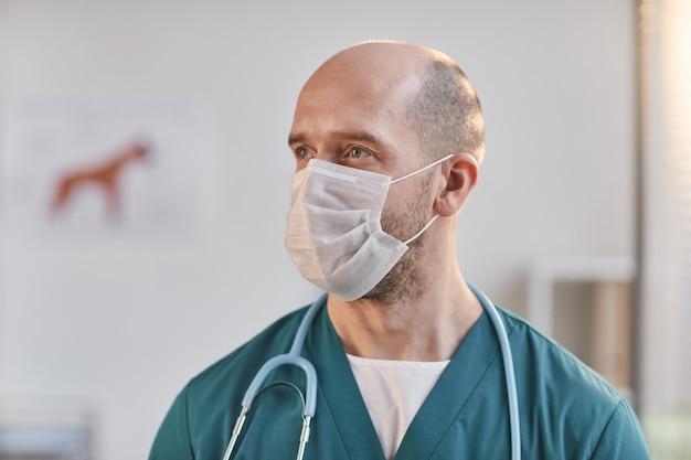 Bliska portret dojrzałego męskiego lekarza weterynarii w masce i odwracając wzrok w klinice weterynaryjnej, kopia przestrzeń