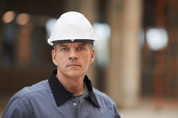Bliska portret dojrzałego pracownika w kasku i stojąc na budowie lub w warsztacie przemysłowym