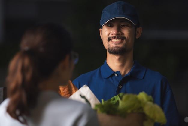 Bliska portret doręczyciela, uśmiechnięty facet w niebieskim mundurze t-shirt, produkty spożywcze zakupy online, nowa koncepcja normalnego stylu życia, sklep detaliczny e-commerce, miejskie życie, transport dostawy.