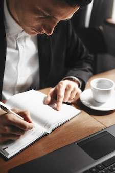 Bliska portret dorosłego menedżera robienia notatek podczas picia filiżanki kawy.