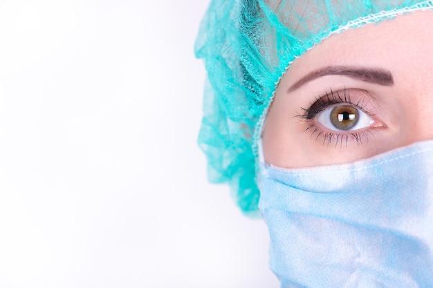 Bliska portret dorosłej kobiety lekarza chirurga na sobie maskę ochronną i czapkę. zbliżenie pół twarzy. koncepcja opieki zdrowotnej, edukacji medycznej, ratownictwa medycznego i chirurgii
