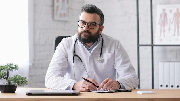 Bliska portret dorosły przystojny lekarz rodzinny w gabinecie lekarskim.