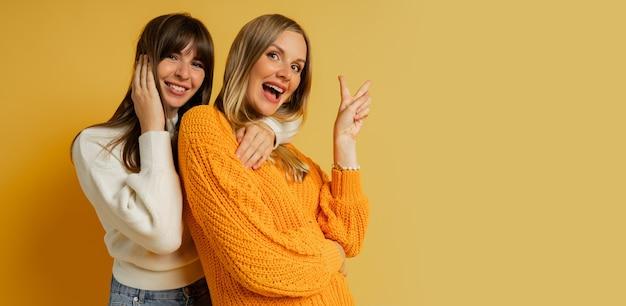 Bliska portret dwóch ładnych kobiet w przytulne swetry pozowanie na żółto. trendy w modzie jesienno-zimowej.