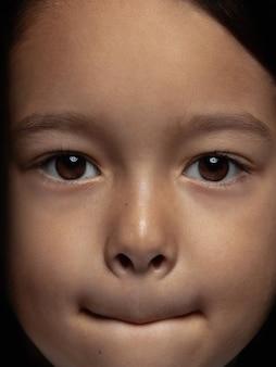 Bliska portret dziewczynki azjatyckie małe i emocjonalne. bardzo szczegółowa sesja zdjęciowa modelki o zadbanej skórze i jasnym wyrazie twarzy. pojęcie ludzkich emocji. wątpliwości, niepewność, wybór.