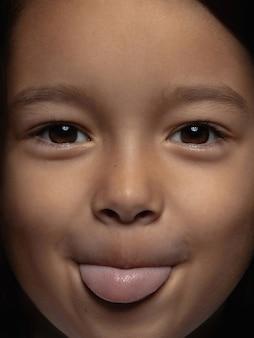 Bliska portret dziewczynki azjatyckie małe i emocjonalne. bardzo szczegółowa sesja zdjęciowa modelki o zadbanej skórze i jasnym wyrazie twarzy. pojęcie ludzkich emocji. wywieszony język.