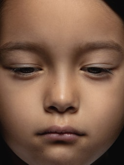 Bliska portret dziewczynki azjatyckie małe i emocjonalne. bardzo szczegółowe zdjęcie modelki o zadbanej skórze i jasnym wyrazie twarzy. pojęcie ludzkich emocji. wygląda na smutnego, zdenerwowanego.