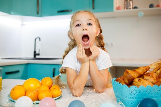 Bliska portret dziewczynki w wieku siedmiu lat. wygłupiać się siedząc przy stole w kuchni. ubrana w białą koszulkę