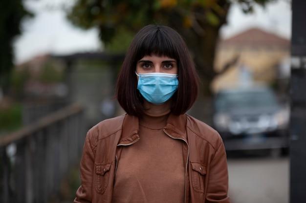 Bliska portret dziewczynki z maską medyczną na zewnątrz podczas kwarantanny krowiej we włoszech