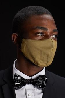 Bliska portret eleganckiego african-american człowieka noszącego maskę, podczas gdy pozuje na czarnym tle na imprezie