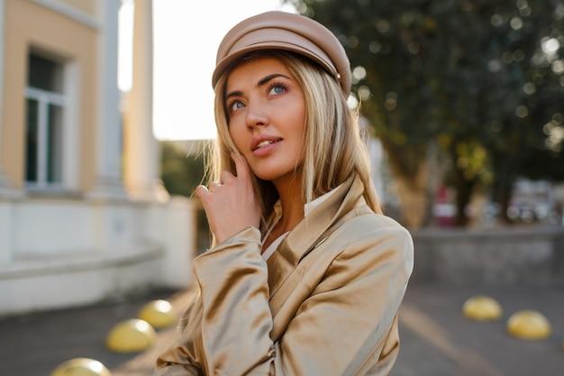 Bliska portret eleganckiej blond kobiety w skórzanym kapeluszu i kurtce na co dzień. blond kobieta pozuje na zewnątrz
