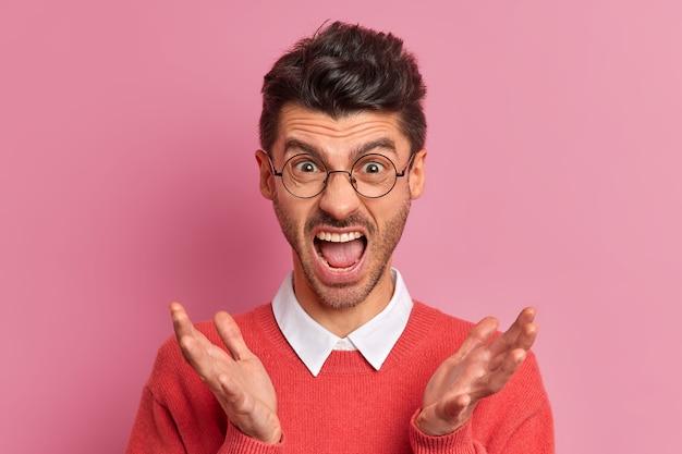 Bliska portret emocjonalnie zirytowanego mężczyzny woła głośno rozkłada dłonie i gesty z irytacją