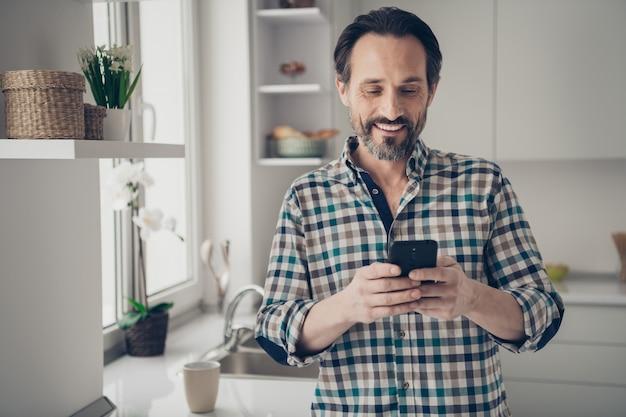 Bliska portret fotograficzny zadowolony pozytywny podekscytowany wesoły przystojny stylowy modny mąż facet dostaje powiadomienie od bliskich krewnych i żony czytającej z uśmiechem na twarzy
