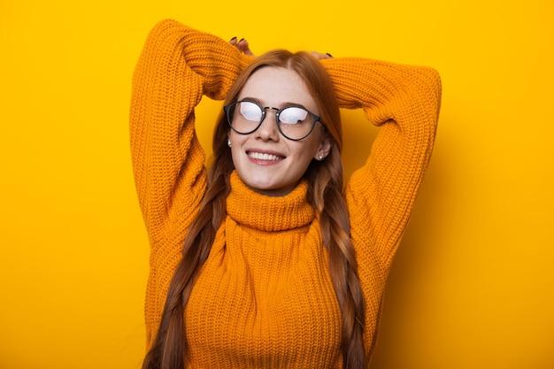 Bliska portret imbir kaukaski dama z piegami w okularach i pozuje rękami na żółtej ścianie