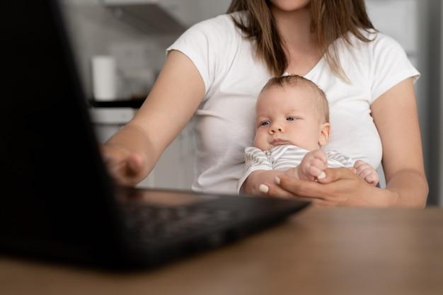 Bliska portret karmiącego dziecka. chłopiec siedzi w ramionach matki. kobieta pracuje w domu z laptopem.