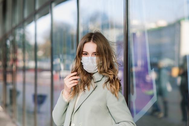 Bliska portret kaukaska kobieta ubrana w maskę medyczną i stojąca na ulicy na tle kawiarni
