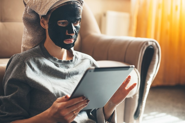 Bliska portret kaukaski kobieta ubrana w czarną maskę w domu i za pomocą tabletu na podłodze