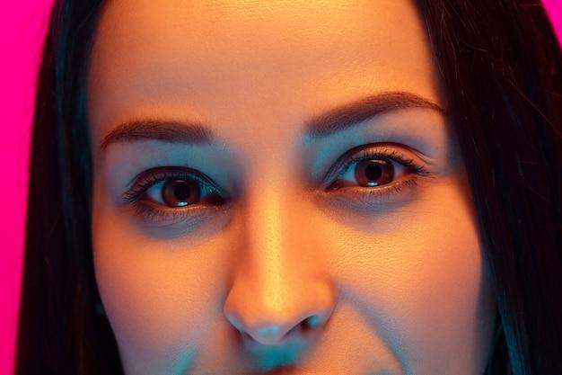 Bliska Portret Kaukaski Kobiety Na Białym Tle Na Tle Różowego Studia W Mieszanym świetle Neonu. Piękna Modelka. Pojęcie Ludzkich Emocji, Wyraz Twarzy, Sprzedaż, Reklama, Moda. Piękno. Darmowe Zdjęcia