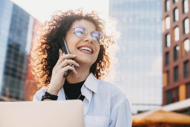 Bliska portret kaukaski przedsiębiorca z kręconymi włosami i okularami rozmawia przez telefon podczas pracy z komputerem na zewnątrz