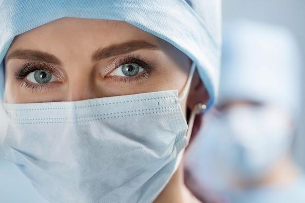 Bliska portret kobiety lekarza chirurga na sobie maskę ochronną i czapkę