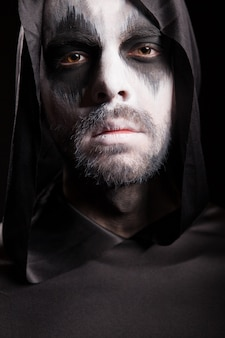 Bliska portret kostucha na białym tle na czarnym tle. kostium na halloween.