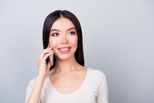 Bliska portret ładna kobieta w strój casual mówi na smartfonie