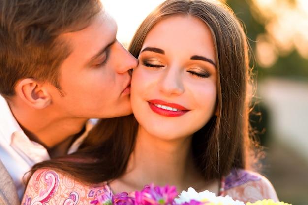 Bliska portret ładna para zakochanych, przystojny chłopak całuje swoją kobietę w policzek, kolory zachodu słońca, jasny makijaż, romantyczna randka rozluźnienie eleganckie ubrania.