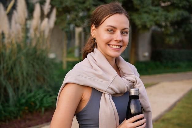 Bliska portret ładnej brunetki kobiety z miękkim naturalnym makijażem pozowanie na zewnątrz