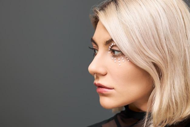 Bliska portret ładnej dziewczyny o blond włosach, przekłuwaniu twarzy i makijażu artystycznym o zamyślonym, zamyślonym wyglądzie, pozuje przed pustą ścianą z miejscem na tekst