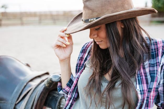 Bliska portret ładnej kowbojki opierając się na płocie na ranczo
