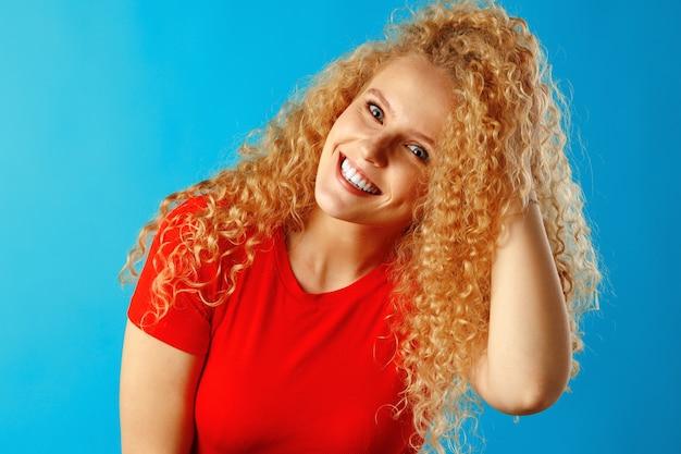Bliska portret ładnej młodej kobiety z długimi kręconymi włosami, wyśmienity
