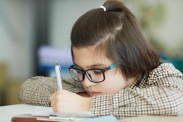 Bliska portret ładny chłopiec w okularach, siedząc przy biurku w szkolnej klasie i pisząc