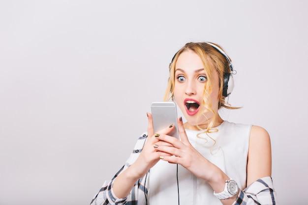 Bliska portret ładny ekstatyczny zadowolony kobieta czytająca coś ekscytującego w swoim smartfonie. emocjonalna blondynka z szeroko otwartymi niebieskimi oczami w białej stylowej bluzce. odosobniony.