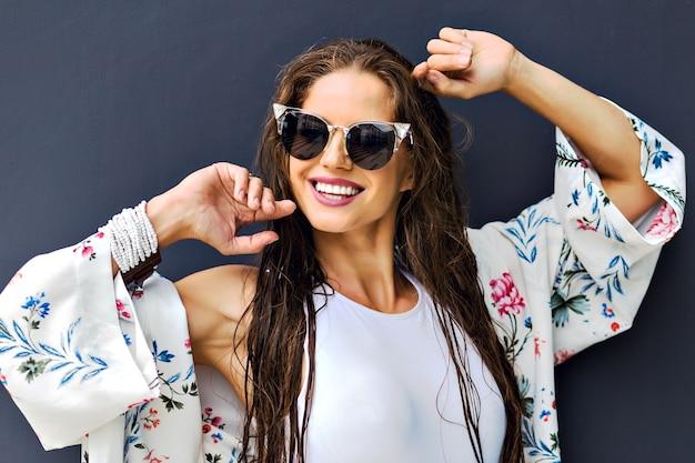 Bliska portret lato moda oszałamiająca brunetka kobieta pozowanie na szarym tle, długie mokre włosy po kąpieli