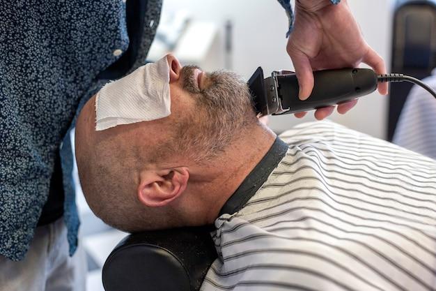 Bliska portret łysego mężczyzny w salonie fryzjerskim podczas przycinania brody