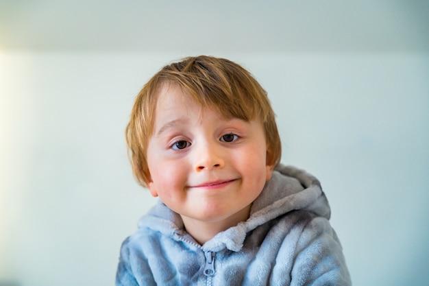 Bliska portret małego chłopca w wieku trzech lat ubrany w ciepły miękki kombinezon patrząc w kamerę, na białym tle na białej ścianie