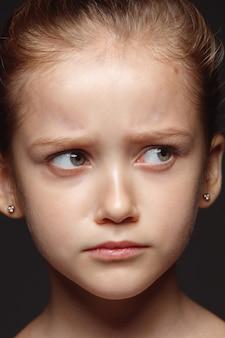 Bliska portret małej i emocjonalnej dziewczyny kaukaski. bardzo szczegółowa sesja zdjęciowa modelki o zadbanej skórze i jasnym wyrazie twarzy. pojęcie ludzkich emocji. smutne, zdenerwowane.