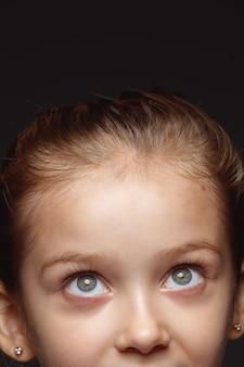 Bliska portret małej i emocjonalnej dziewczyny kaukaski. bardzo szczegółowa sesja zdjęciowa modelki o zadbanej skórze i jasnym wyrazie twarzy. pojęcie ludzkich emocji. wymarzone spojrzenie w górę.