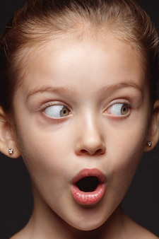 Bliska portret małej i emocjonalnej dziewczyny kaukaski. bardzo szczegółowa sesja zdjęciowa modelki z zadbaną skórą i jasnym wyrazem twarzy. pojęcie ludzkich emocji. zdziwiony, patrząc z boku.