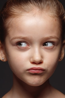 Bliska portret małej i emocjonalnej dziewczyny kaukaski. bardzo szczegółowe zdjęcie modelki o zadbanej skórze i jasnym wyrazie twarzy. pojęcie ludzkich emocji. przemyślane, myślące.