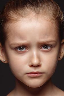 Bliska portret małej i emocjonalnej dziewczyny kaukaski. bardzo szczegółowe zdjęcie modelki o zadbanej skórze i jasnym wyrazie twarzy. pojęcie ludzkich emocji. smutne, zdenerwowane.