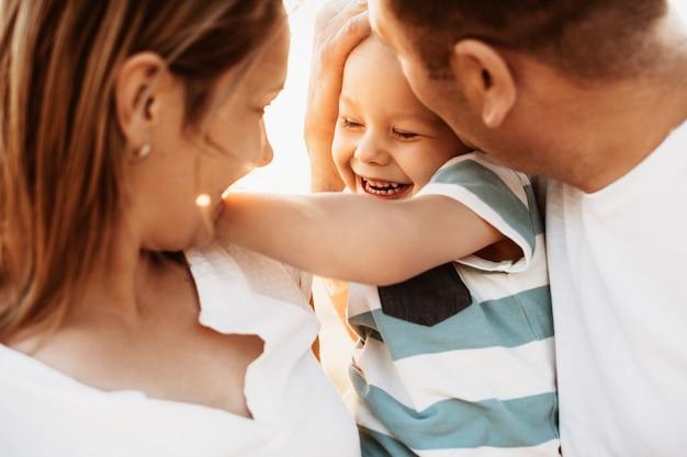 Bliska portret matki i ojca całujących syna, obejmując na zewnątrz.