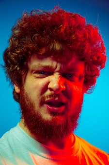 Bliska portret mężczyzny na białym tle na ścianie w niebieskim studio w czerwonym świetle neonu