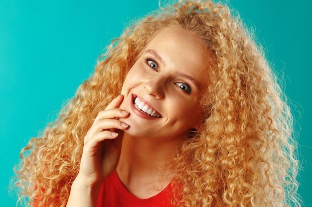 Bliska portret miłej młodej kobiety z długimi kręconymi włosami