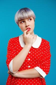 Bliska portret miło piękna lalka dziewczyna z krótkimi jasnofioletowymi włosami na sobie czerwoną sukienkę na niebieską ścianą