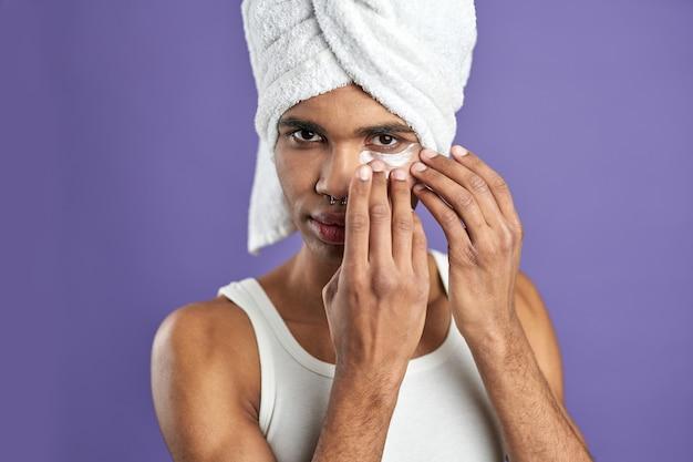 Bliska portret młodego afroamerykanina użyj łaty przeciwzmarszczkowej żel do oczu w ręczniku kąpielowym