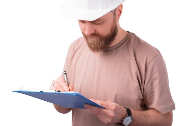 Bliska portret młodego architekta mężczyzny w białym kasku i sporządzanie notatek na papierze