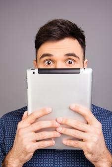 Bliska portret młodego biznesmena, ukrywając twarz za tabletem